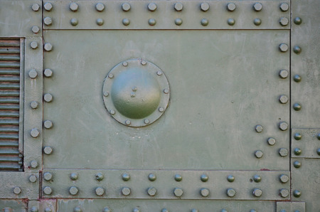 The texture of the wall of the tank, made of metal and reinforced with a multitude of bolts and rivets. Images of the covering of a combat vehicle from the Second World War Stock Photo