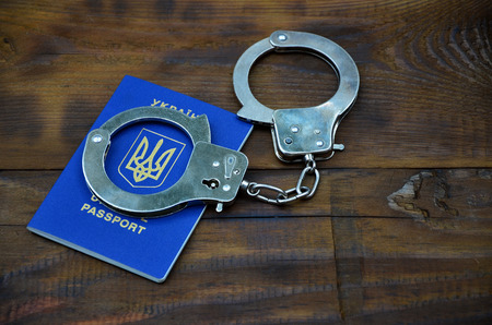 Ukrainian passport with police handcuffs lies on a wooden table. The concept of crime of Ukrainian citizens when traveling abroad. Illegal activities during travel