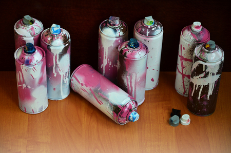 Still life with a large number of used colorful spray cans of aerosol paint lying on the treated wooden surface in the artists graffiti workshop. Dirty and stained cans for spray art