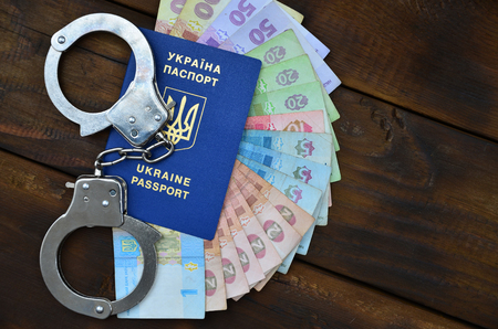 A photograph of a Ukrainian foreign passport, a certain amount of Ukrainian money and police handcuffs. The concept of arresting Ukrainian illegal immigrants while trying to bribe