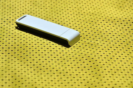 A modern portable USB internet adapter is placed on the yellow sportswear made of polyester nylon fiber Stock Photo