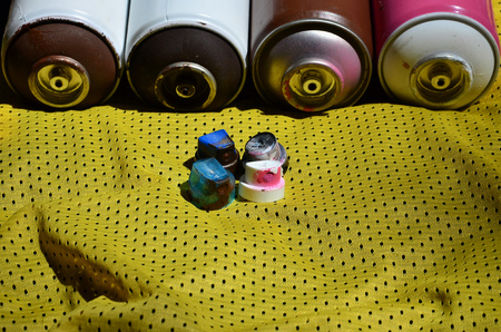Several caps for used aerosol paint sprayers lie on the sports shirt of a basketball player made of polyester fabric. The concept of youth street art, active sports and eventful lifestyle