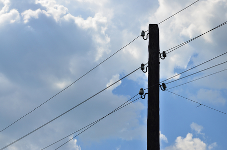 Old wooden electric pole for transmission of wired electricity on a background of a cloudy blue sky. Obsolete method of supplying electricity for later use