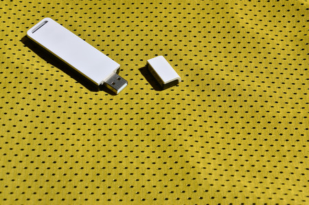 A modern portable USB adapter is placed on the yellow sportswear made of polyester nylon fiber