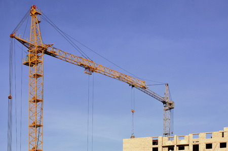 Working tall cranes inside place for with tall buildings under construction against a clear blue sky.