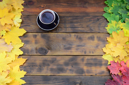 A cup of tea among a set of yellowing fallen autumn leaves on a background surface of natural wooden boards of dark brown color
