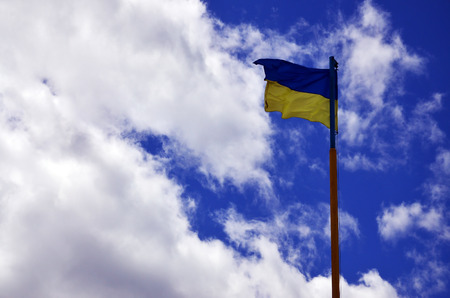 Ukrainian flag against the blue sky with clouds. The official flag of the Ukrainian state includes yellow and blue colors Stock Photo