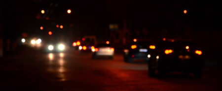 Artistic style - Defocused urban abstract texture, blurred background with bokeh of city lights from car on street at night, vintage or retro color tone