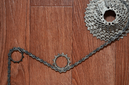 Some composition of a bicycle chain, several sprockets and other components of a sports bike. Metal and dirty bicycle parts on a brown wooden background