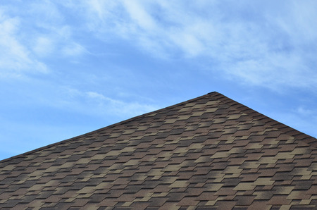 The roof of a residential house, covered with a modern flat bituminous waterproof coating under a blue cloudy sky. The concept of high-quality roofing with bituminous coating