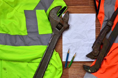 A crumpled sheet of paper with two pencils surrounded by green and orange working uniforms and adjustable wrenches. Still life associated with repair, railway or plumbing works Stock Photo
