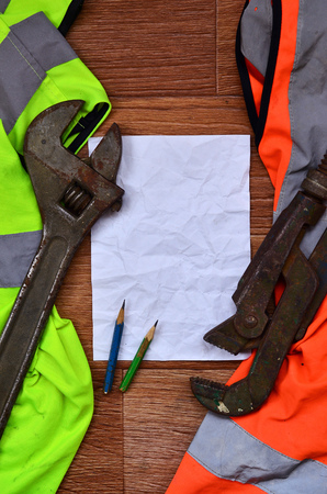 A crumpled sheet of paper with two pencils surrounded by green and orange working uniforms and adjustable wrenches. Still life associated with repair, railway or plumbing works Stock fotó