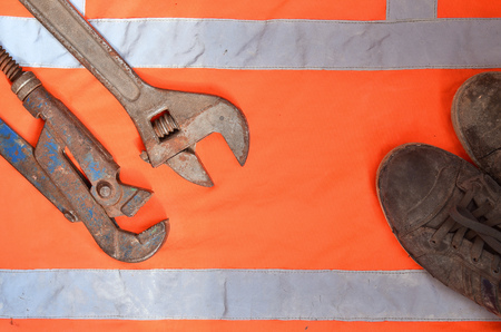 Adjustable and pipe wrenches against the background of an orange signal worker shirt. Still life associated with repair, railway or plumbing works Imagens