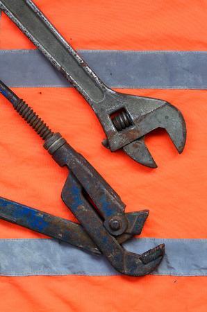 Adjustable and pipe wrenches against the background of an orange signal worker shirt. Still life associated with repair, railway or plumbing works Stock fotó