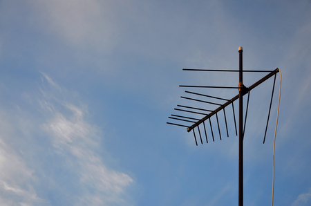 An old and rusty television antenna against a cloudy blue sky. Obsolete device for receiving a television signal in private houses