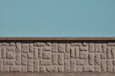 The horizontal texture of the foundation in the form of a mosaic made of a dark, coarse and strong granite stone in the sunlight outdoors