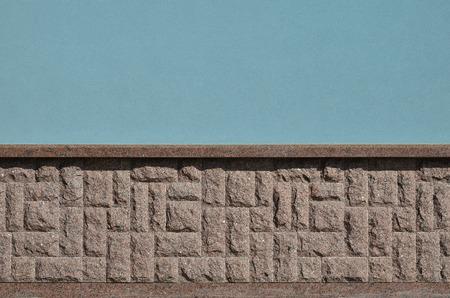 De horizontale textuur van de basis in de vorm van een mozaïek gemaakt van een donkere, ruwe en sterke granieten steen in het zonlicht buiten