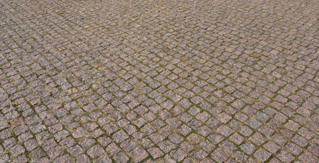 Cobbles texture - hard pavement, a kind of pavement, laid out by flat rectangular (or other shape) bars of approximately the same shape and size Stock Photo