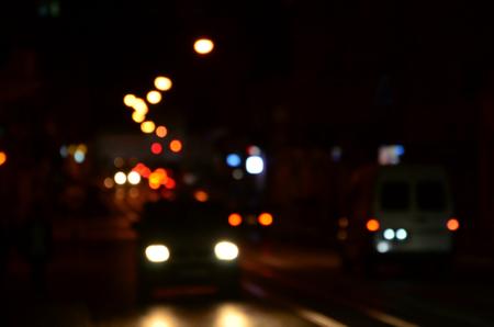 Blurred night scene of traffic on the roadway. Defocused image of cars traveling with luminous headlights. Bokeh Art Stock Photo