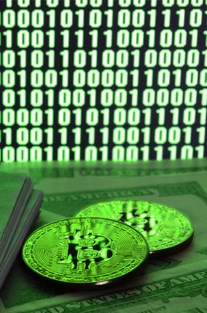Two bitcoins lies on a pile of dollar bills on the background of a monitor depicting a binary code of bright green zeros and one units on a black background. Low key lighting