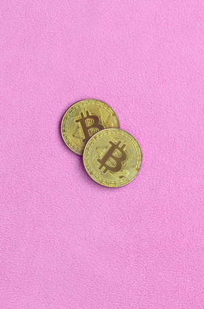 Two golden bitcoins lies on a blanket made of soft and fluffy light pink fleece fabric. Physical visualization of virtual crypto currency 写真素材