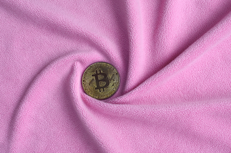 The golden bitcoin lies on a blanket made of soft and fluffy light pink fleece fabric with a large number of relief folds. The shape of the folds resembles a fan from a video card cooler Banque d'images