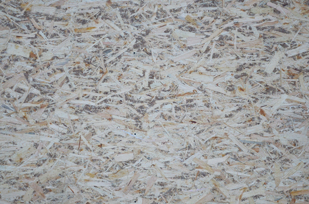 An old oriented strand board (OSB), fiberboard background of texture. Sheet is made of brown wood chips pressed together into a wooden floor Stock Photo