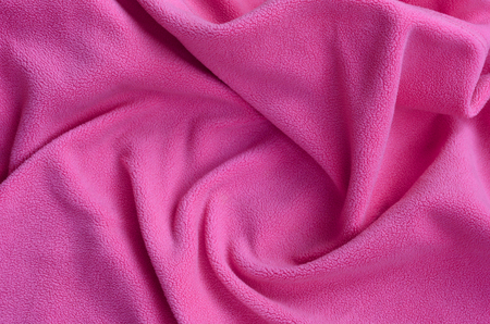 The blanket of furry pink fleece fabric. A background of light pink soft plush fleece material with a lot of relief folds