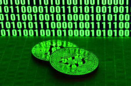 A pair of bitcoins lies on a cardboard surface on the background of a monitor depicting a binary code of bright green zeros and one units on a black background. Low key lighting