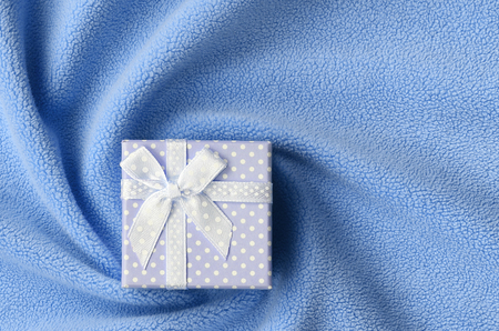 A small gift box in blue with a small bow lies on a blanket of soft and furry light blue fleece fabric with a lot of relief folds. Packing for a gift to your lovely girlfriend Archivio Fotografico