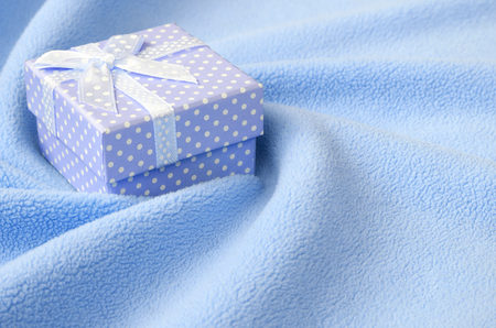 A small gift box in blue with a small bow lies on a blanket of soft and furry light blue fleece fabric with a lot of relief folds. Packing for a gift to your lovely girlfriend Foto de archivo