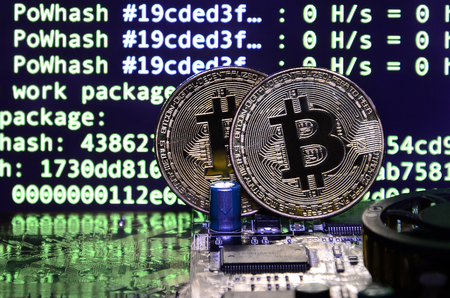 Two bitcoins lies on a videocard surface with background of screen display of cryptocurrency mining by using the GPUs Foto de archivo