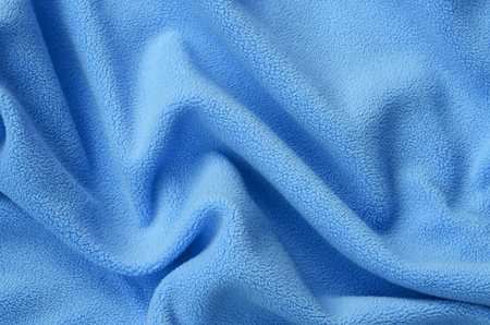 The blanket of furry blue fleece fabric. A background of light blue soft plush fleece material with a lot of relief folds