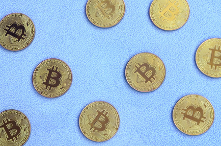 Many golden bitcoins lies on a blanket made of soft and fluffy light blue fleece fabric. Physical visualization of virtual crypto currency