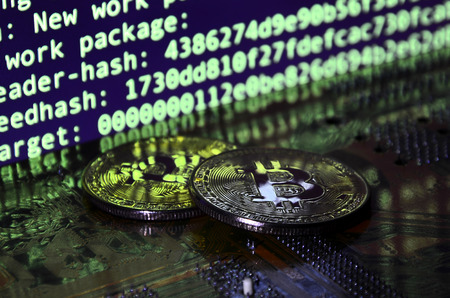 The digital process of cryptocurrency mining by using the GPUs. Bitcoins and video card on a working display and mining screen