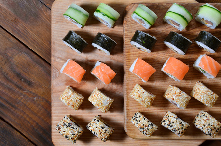 Sushi set of a number of rolls is located on a wooden cutting board on a table in the kitchen of a sushi bar. A traditional dish of oriental cuisine