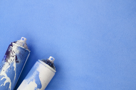 Some used blue aerosol spray cans with paint drips lies on a blanket of soft and furry light blue fleece fabric. Classic female design color. Graffiti hooliganism concept Reklamní fotografie