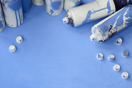 Some used blue aerosol spray cans and nozzles with paint drips lies on a blanket of soft and furry light blue fleece fabric. Classic female design color. Graffiti hooliganism concept 写真素材