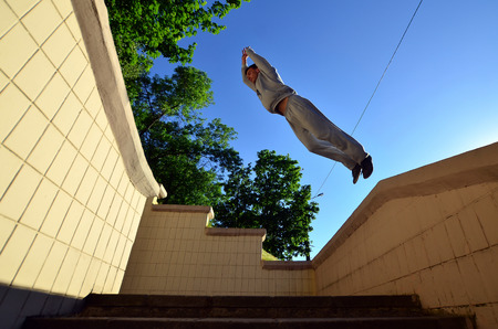 A young guy performs a jump through the space between the concrete parapets. The athlete practices parkour, training in street conditions. Bottom view
