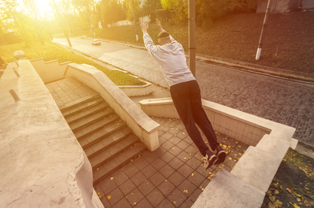 A young guy performs a jump through the space between the concrete parapets. The athlete practices parkour, training in street conditions. The concept of sports subcultures among youth 写真素材