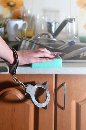 The hand of a young girl with a kitchen sponge, handcuffed to a kitchen counter with a lot of unwashed dishes, plates, cups and cutlery. The concept of forcing women to work in the kitchen