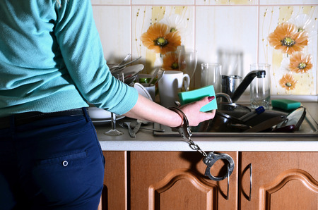 A girl with a sponge in her hand, handcuffed to the kitchen counter with a sink filled with a bunch of unwashed dishes. Female slavery of the kitchen. The problem of daily hand-washing dishes
