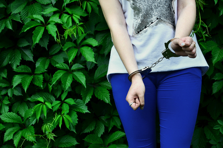 Fragment of a young criminal girls body with hands in handcuffs against a green blossoming ivy leaves background. The concept of detaining an offender of a female criminal in a rural environment
