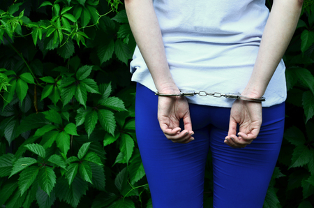 Fragment of a young criminal girl's body with hands in handcuffs against a green blossoming ivy leaves background. The concept of detaining an offender of a female criminal in a rural environment 스톡 콘텐츠