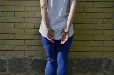 Fragment of a young criminal girls body with hands in handcuffs against a yellow brick wall background. The concept of detaining an offender of a female criminal in an urban environment