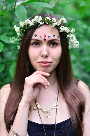 Portrait of an emotional young girl with a floral wreath on her head and shiny ornaments on her forehead. Cute brunette posing in a burgeoning beautiful forest in the daytime on a fine day
