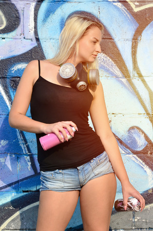 A young and beautiful sexy girl graffiti artist with a paint spray and gas mask on her neck stands on the wall background with a graffiti pattern in blue and purple tones Stock Photo