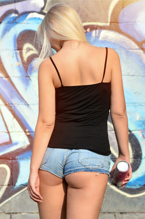 A rear view of a young and beautiful sexy blonde girl graffiti artist with a paint spray stands on the wall background with a graffiti pattern in blue and purple tones Stock Photo