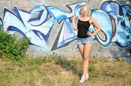 Sexy Kaukasisch blondemeisje in denimborrels en het zwarte mouwloos onderhemd stellen tegen graffitimuur in de dag in openlucht Stockfoto