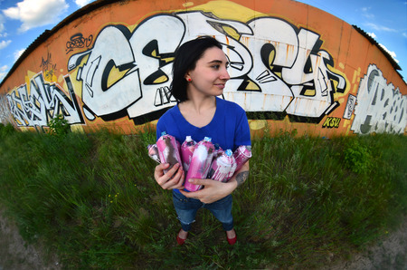 Portrait of an emotional young girl with black hair and piercings. A wide-angle photo of a girl with aerosol paint cans in the hands on a graffiti wall background. A modern portrait of a fisheye lens